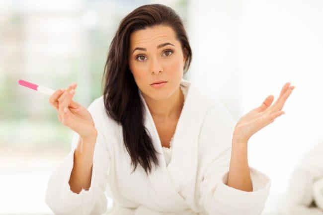 Женщина в белом халате держащая тест для определения беременности