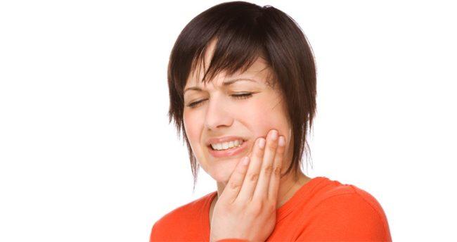 Зубная боль у женщины с короткими волосами на белом фоне