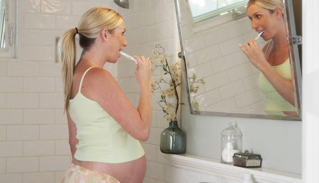 Беременная женщина соблюдающая гигиену области рта