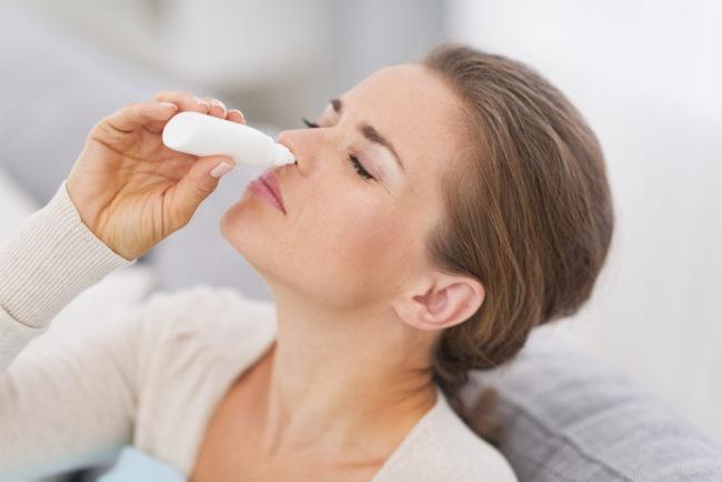 Девушка капает в нос капли от насморка