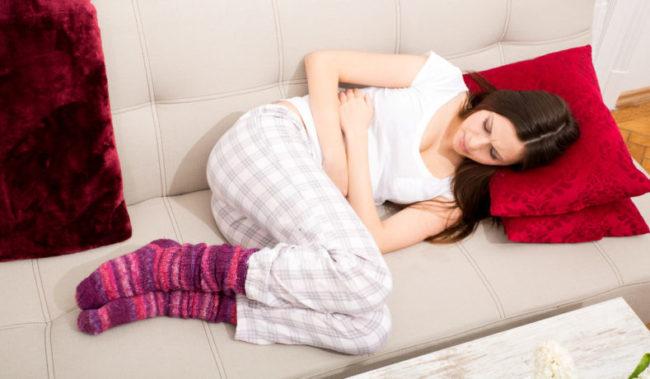 Девушка лежащая на диване в период менструации