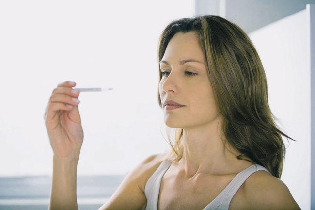Женщина с длинными волосами держащая в руках градусник