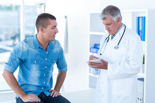 Мужчина в синей рубашке на осмотре у врача