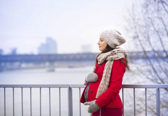 Беременная женщина гуляющая в холодное время года