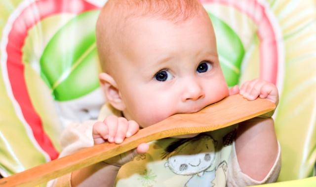 Ребёнок сидит в зеленом стульчике и чешет зубки о кухонную деревянную лопатку