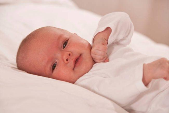 Новорожденный мальчик в белой одежде