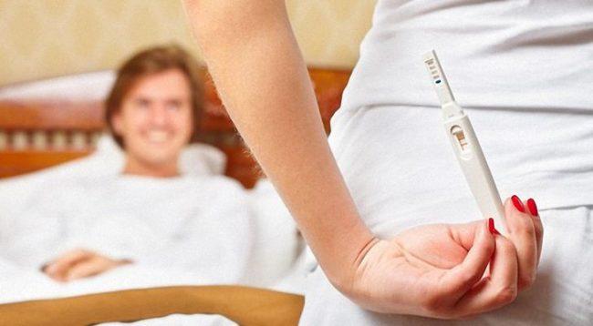 Девушка держит за спиной тест на беременность