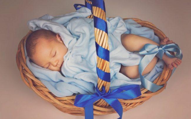 Мальчик новорожденный в синем одеяле в корзинке