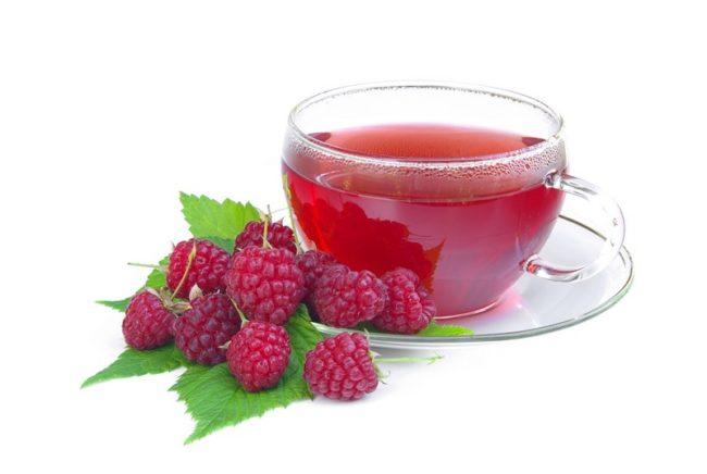 Малиновый чай в прозрачной чашке и ягода малина