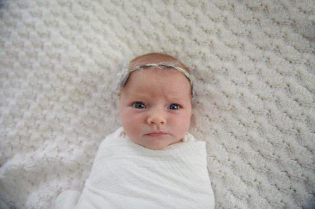 Новорождённая девочка в белой простыне