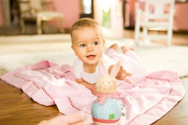 Девочка пяти месяцев в розовой одежде на полу