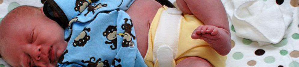Новорождённый лежит в памперсе