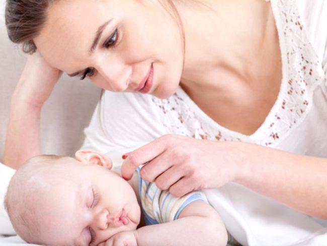 Спящий новорождённый рядом с мамой