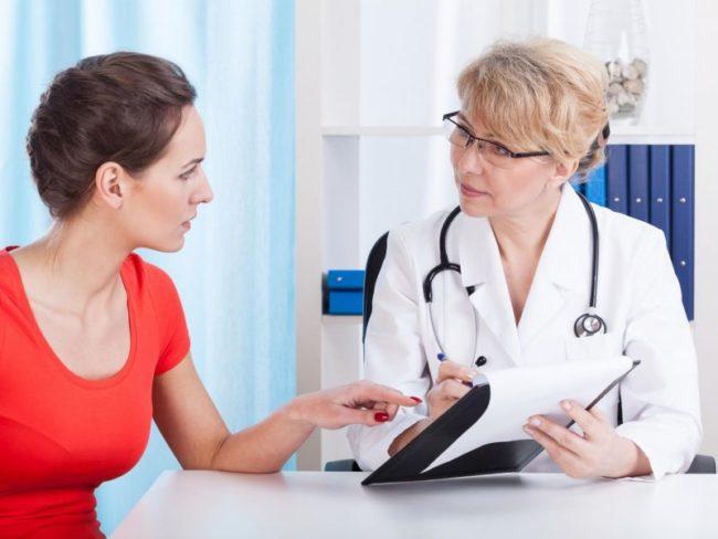 Женщина в красной кофте на приеме у врача в белом халате