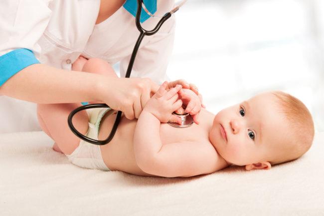 Малыш у врача педиатра прослушиваемый стетоскопом