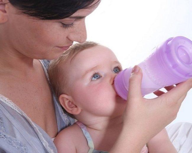 Ребёнок употребляющий укропную воду из бутылочки