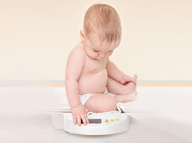 Ребенок в подгузниках на белых весах