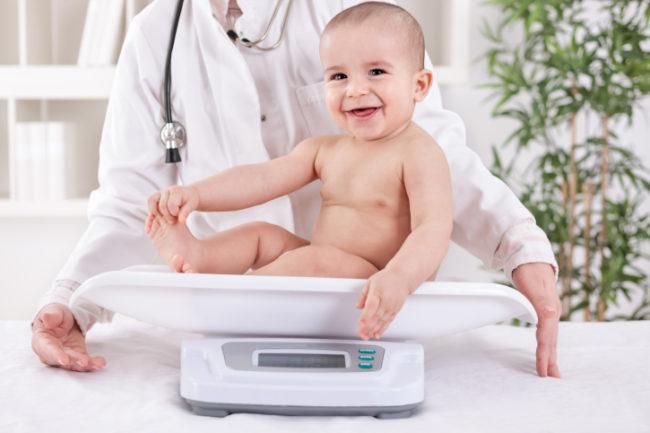 Малыш на белых весах и врач в халате