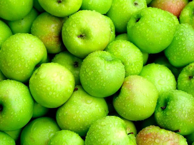 Много зелёных мытых яблок