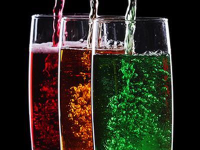 Стаканы с различными красными желтыми и зелеными газированными напитками