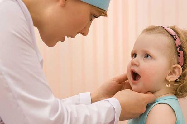 Новорождённая девочка показывает горло на осмотре у врача
