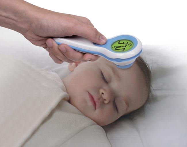 Измерение температуры у новорождённого ребёнка инфракрасным электронным градусником у лба