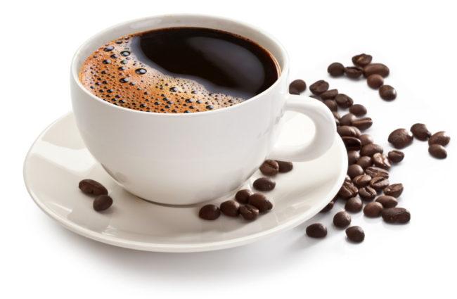 Кофе в белой чашке и зёрна на столе