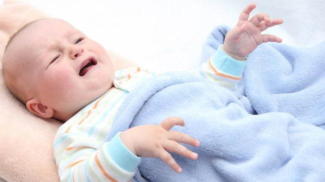 Новорождённый ребёнок от боли поджал ножки и ручки