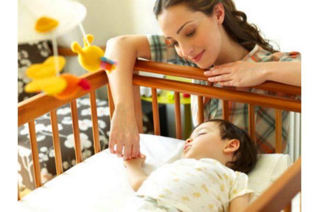 Мама держит новорождённого сладко спящего ребёнка за ручку в своей кроватке