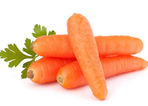Оранжевая морковь с ботвой крупным планом