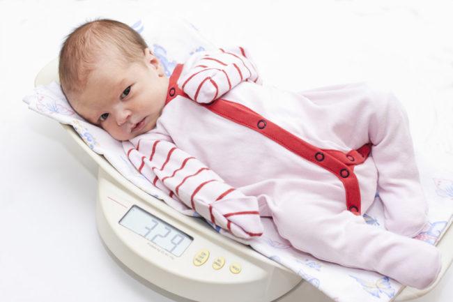 Новорождённый лежащий на весах