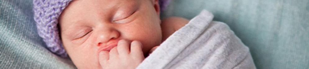 Новорождённый в пелёнке спит и сосёт палец