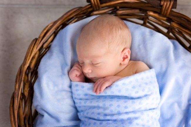 Новорождённый малыш в голубом одеяле