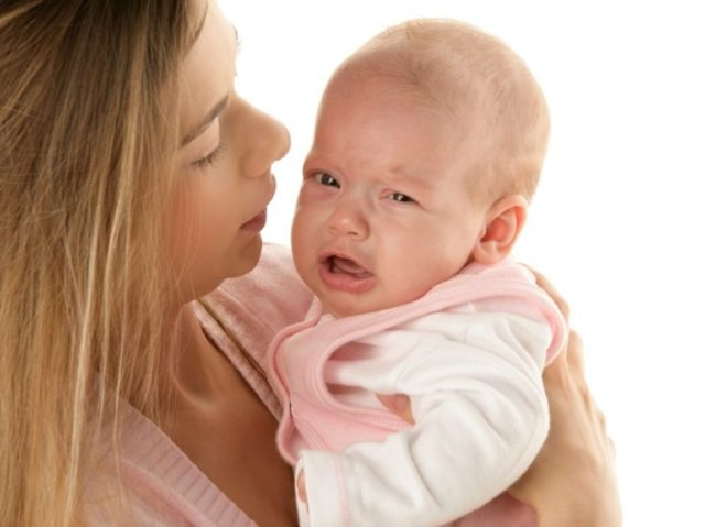 Капризный малыш на руках мамы