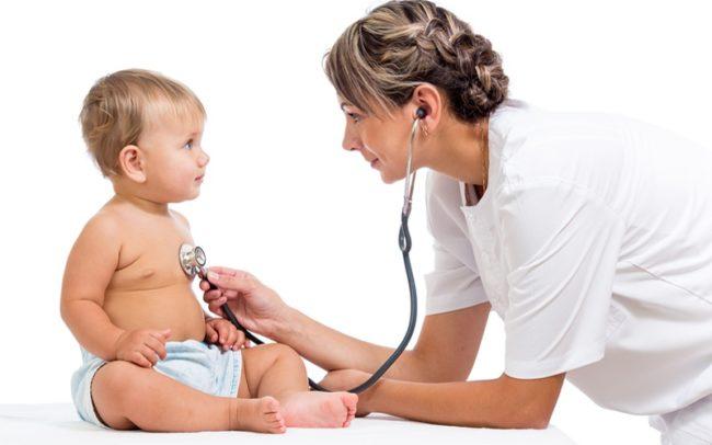 Детский врач педиатр слушает стетоскопом новорождённого ребёнка