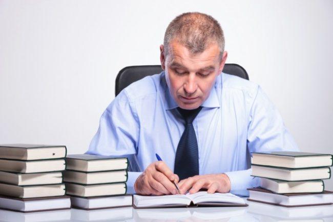 Мужчина в галстуке за столом с книгами