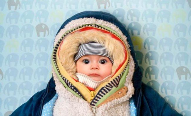 Ребёнок лежит укутанный в детский теплый костюм