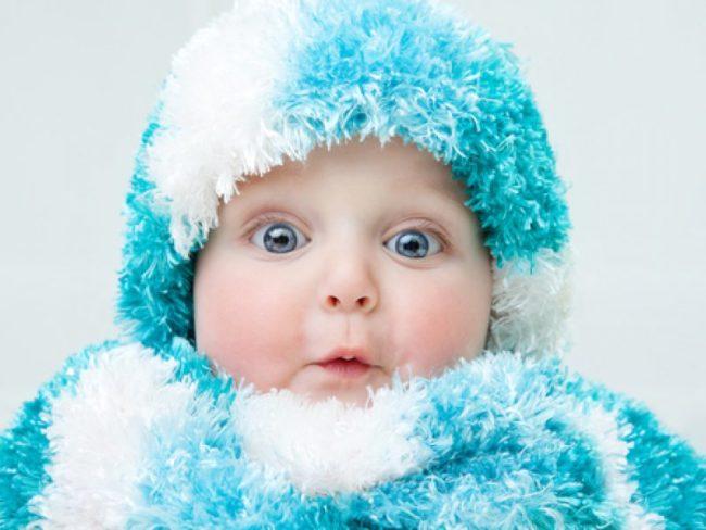 Новорождённый ребёнок в шапочке и шубке из голубой травки