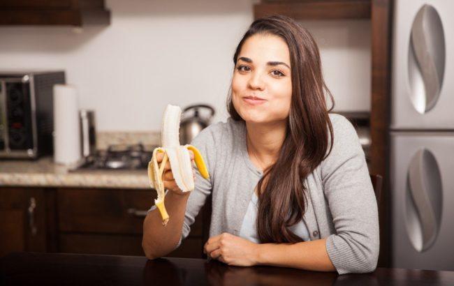 Женщина на кухне и жёлтый банан в руке