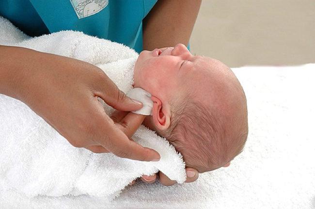 Протирание за ушками у малыша после купания