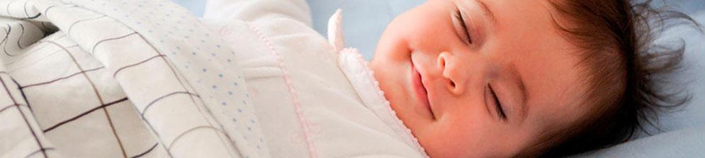 Новорождённый спит в кроватке