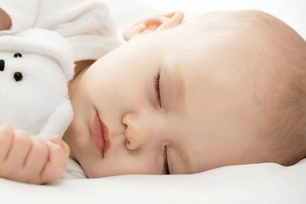 Новорождённый ребёнок спит в обнимку с игрушечным зайчиком