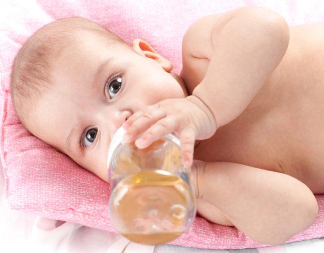 Новорождённый и сок в бутылочке