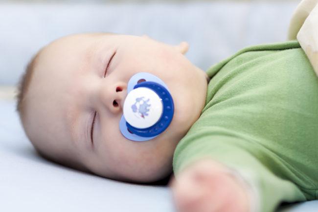 Новорождённый ребёнок сладко спит с синей пустышкой во рту
