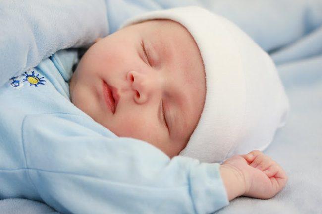 Новорождённый спящий в шапочке