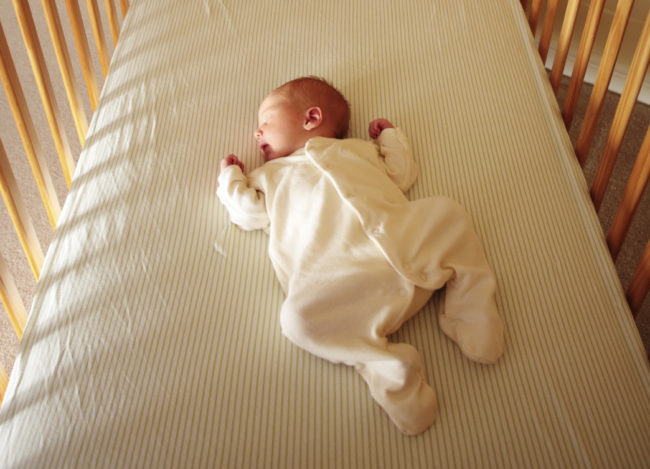 Новорождённый спит в детской кроватке