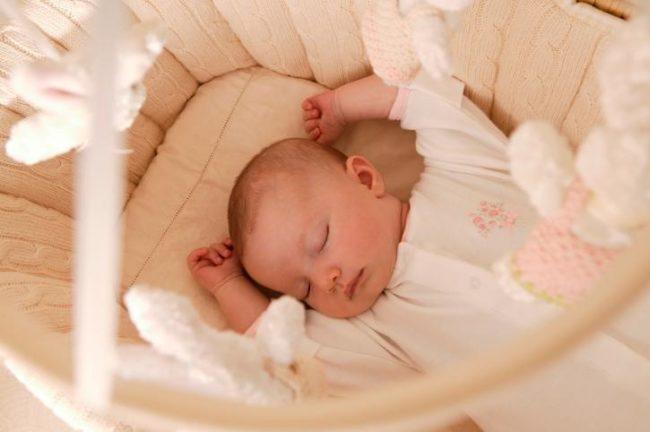 Спящий новорождённый в кроватке