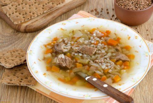 Суп из мяса с гречкой и хлебцами в белой тарелке