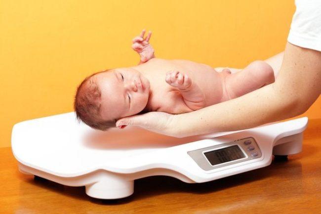 Новорождённый на руках и весы