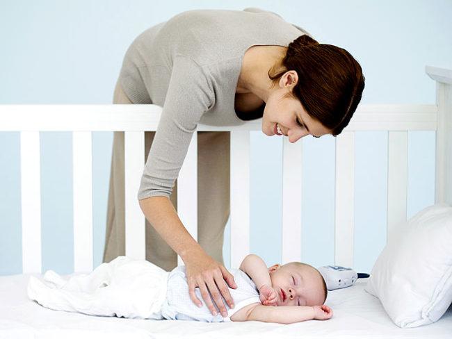 Спящий новорождённый в кроватке и мама